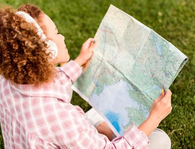 Hoge hoekvrouw die een kaart voor haar nieuwe bestemming controleert