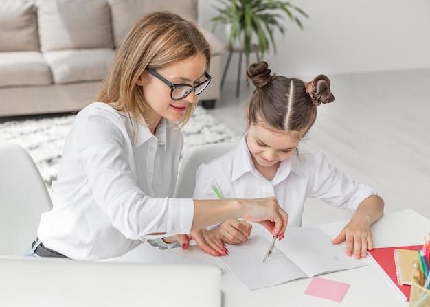 Hoge hoekvrouw die haar dochter met huiswerk helpt