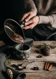 Hoge hoekvrouw die hete chocolademelk zuivert in mag met pan