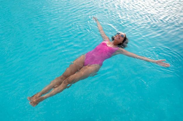 Hoge hoekvrouw die in het zwembad drijft
