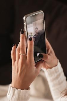 Hoge hoekvrouw die mobiel model houdt