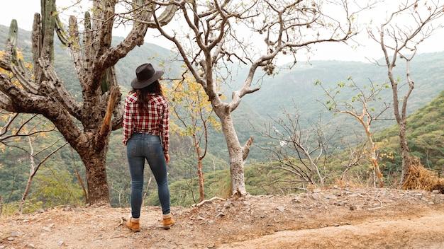 Hoge hoekvrouw die onderaan de vallei kijkt
