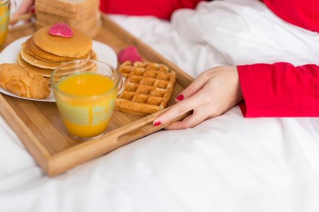 Hoge hoekvrouw die ontbijt in bed dient