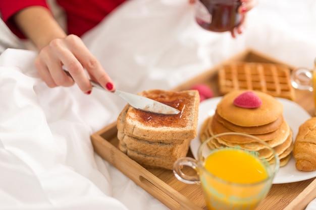 Hoge hoekvrouw die ontbijt in bed eet