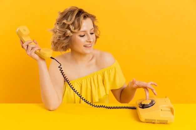 Hoge hoekvrouw die oude telefoon met behulp van