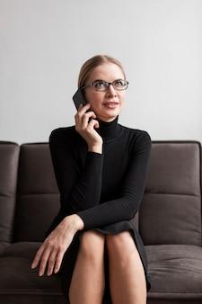 Hoge hoekvrouw die over telefoon spreekt
