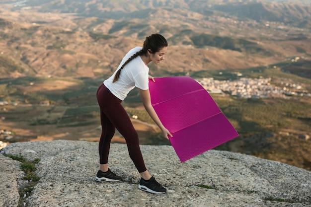 Hoge hoekvrouw die voor yoga voorbereidingen treft