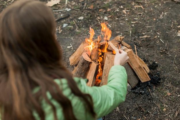 Hoge hoekvrouw die vuur maakt