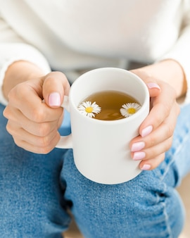 Hoge hoekvrouw die witte mok met thee en bloemen houdt