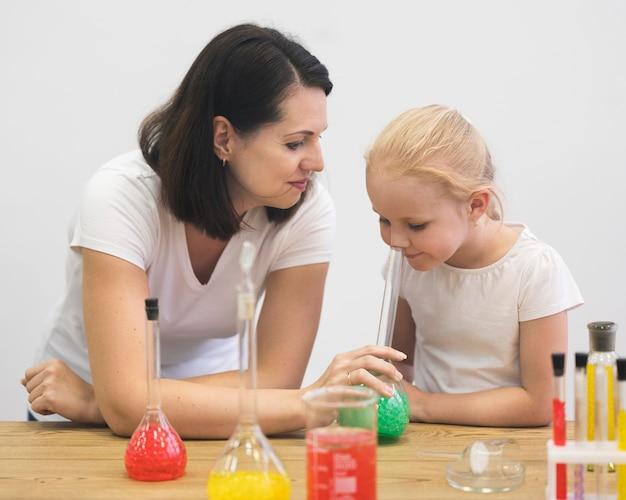 Hoge hoekvrouw en meisje die experiment controleren