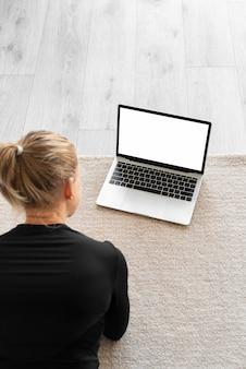 Hoge hoekvrouw met laptop binnenshuis