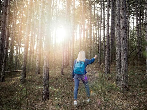 Hoge hoekvrouw met rugzak in bos