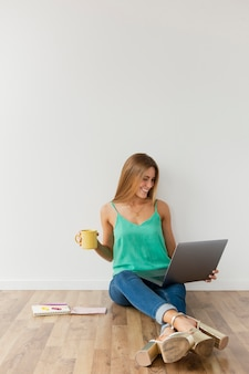 Hoge hoekvrouw op vloer die aan laptop werkt