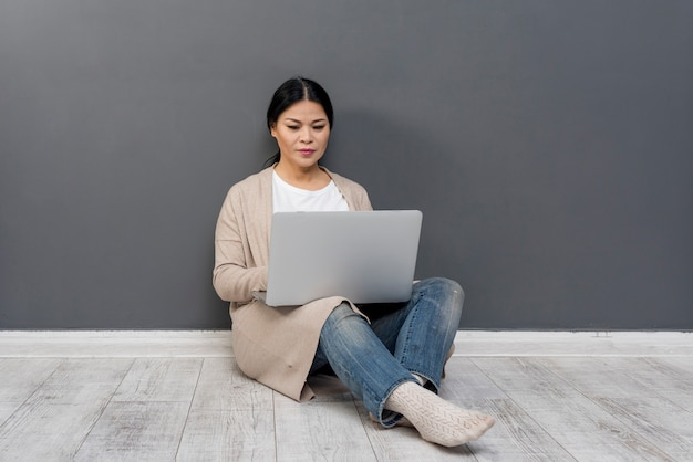 Hoge hoekvrouw op vloer met laptop