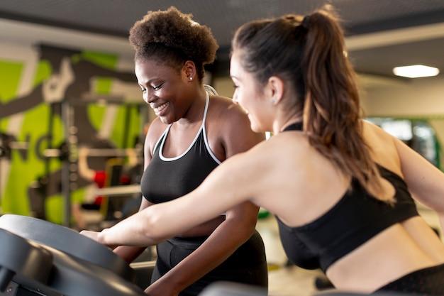 Hoge hoekvrouwen bij gymnastiek die samen opleiden