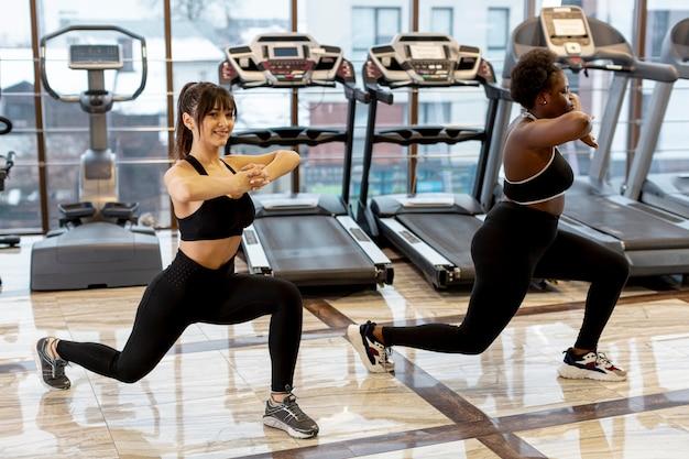 Hoge hoekvrouwen bij gymnastiek die samen uitwerken