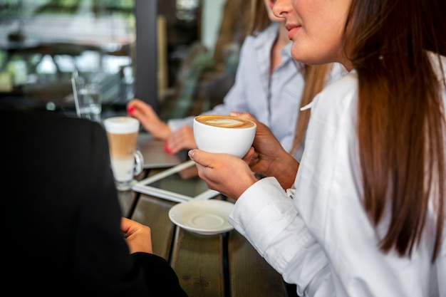 Hoge hoekvrouwen die en koffie werken drinken