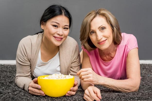 Hoge hoekvrouwen op vloer met kom popcorn