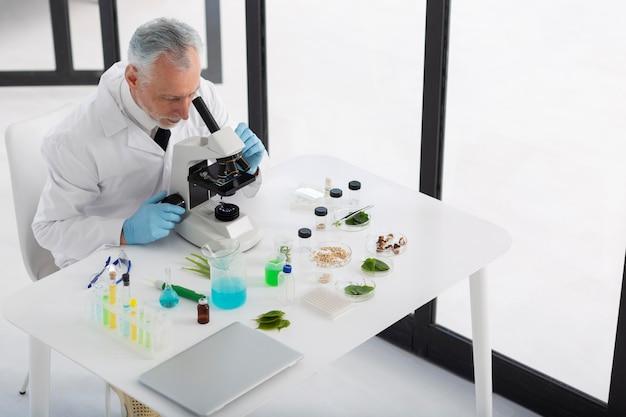 Hoge hoekwetenschapper die met microscoop werkt
