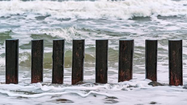 Hoge houten golfbrekers in blauwe schuimende zeegolven, close-up. lange palen of kribben in het water. stormachtige dag op zee.