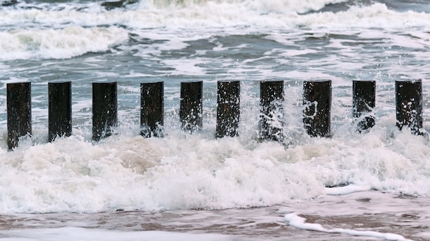 Hoge houten golfbrekers in blauwe schuimende zeegolven, close-up. lange palen of kribben in water
