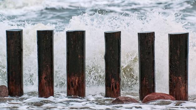 Hoge houten golfbrekers in blauwe spetterende zeegolven, close-up. lange palen of kribben in het water. stormachtige dag op zee.