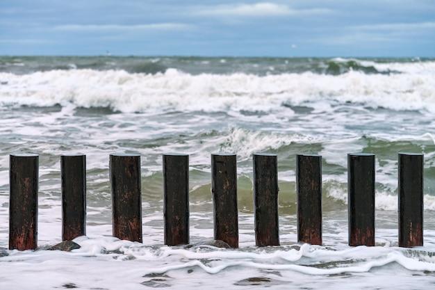 Hoge houten golfbrekers in spattende golven van de zee, mooie bewolkte hemel, close-up uitzicht. lange palen of kribben in stormachtige zee.
