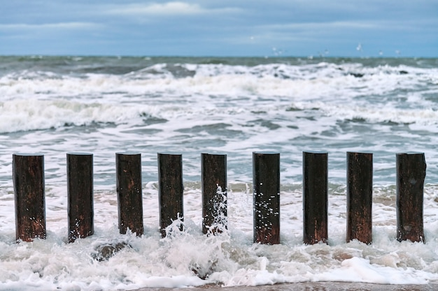 Hoge houten golfbrekers in spattende zeegolven, mooie bewolkte hemel