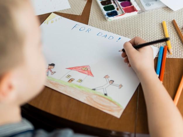 Hoge kijk kind en tekeningen voor zijn vader