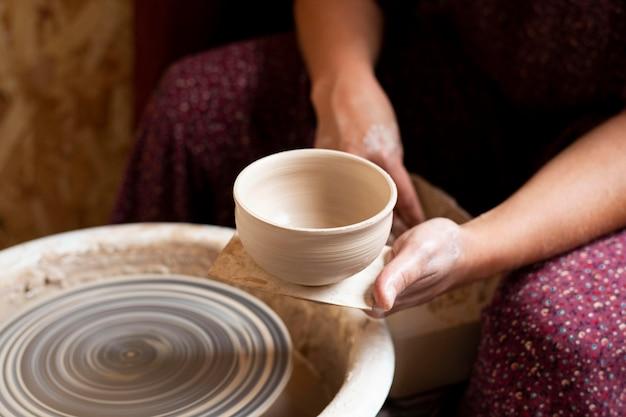 Hoge kijkkom gemaakt van klei op een pottenbakkersschijf