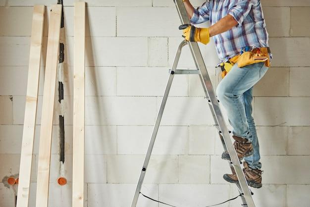 Hoge ladder als ondersteuning voor timmermanswerker
