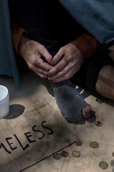 Hoge mening bedelaar persoon met munten en gaten in sokken
