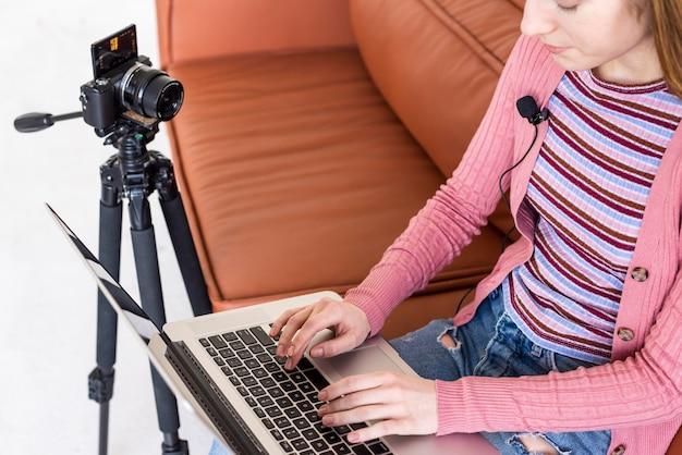 Hoge mening blogger zittend op de bank met behulp van haar laptop