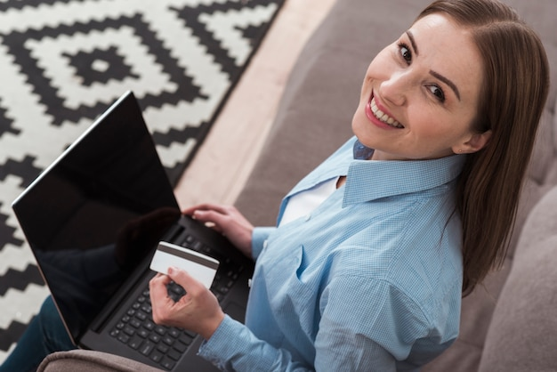 Hoge mening smileyvrouw die haar laptop met behulp van om online producten te kopen