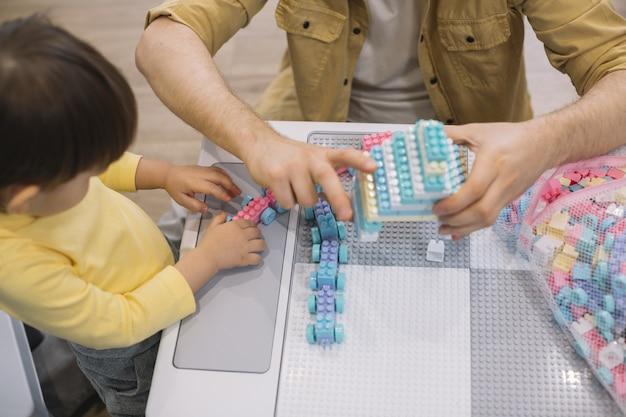 Hoge mening vader en zoon spelen met speelgoed
