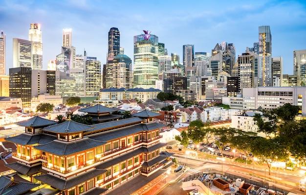 Hoge mening van de horizon van singapore met wolkenkrabbers en de tempel van het tandrelikwie op blauw uur