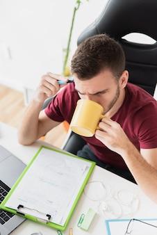 Hoge mening van kerel die en een koffie denkt drinkt