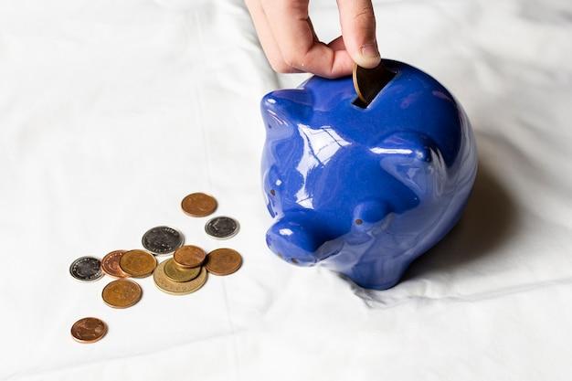 Hoge meningshand die muntstukken in een spaarvarken zet