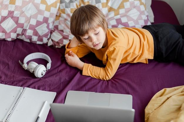 Hoge meningsjongen die van zijn laptop leert