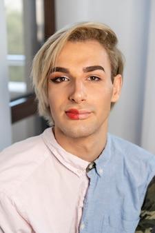 Hoge meningsmens die make-up op de helft van zijn gezicht draagt