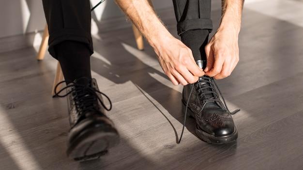 Hoge meningspersoon die zijn schoenveters vasthoudt