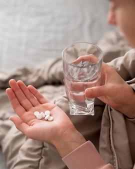 Hoge meningsvrouw die pillen in haar hand heeft