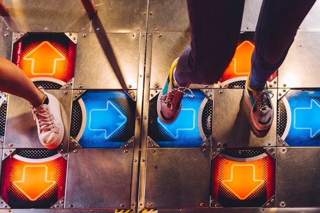 Hoge meningsvrouwen die dansende arcade spelen