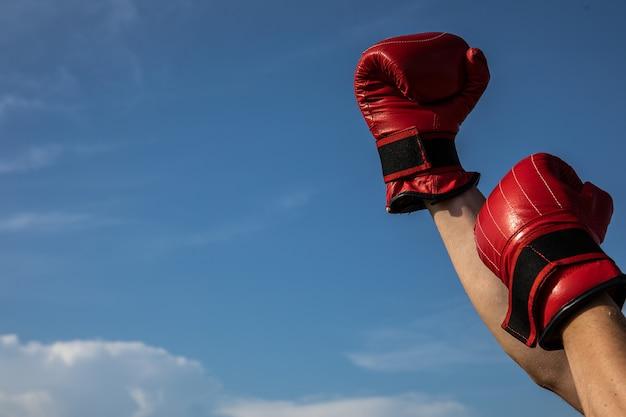 Hoge resolutie foto van mannenhand met rode bokshandschoenen op de bewolkte blauwe hemel.