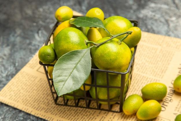Hoge resolutie foto van zwarte mand met verse groene mandarijnen en kumquats op kranten op grijze achtergrond