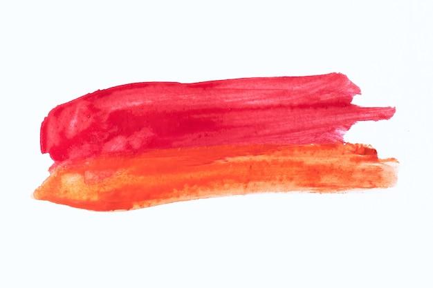 Hoge resolutie textuur van rode en oranje penseelstreken op witte achtergrond.