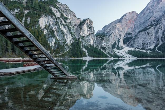 Hoge rotsachtige bergen weerspiegeld in braies-meer met houten treden dichtbij de pijler in italië