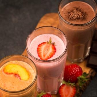 Hoge selectiehoek van milkshakeglazen met chocolade en fruit