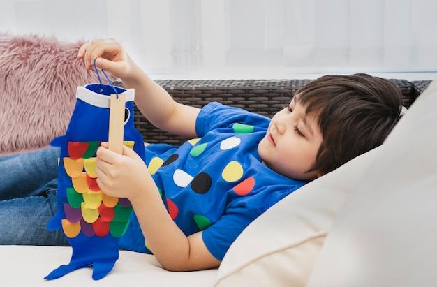 Hoge sleutel gelukkig kind thuis liggend op de bank spelen koinobori (karper streamers), kind jongen doet japanse visvlieger
