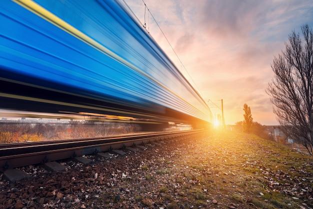 Hoge snelheid blauwe passagierstrein op spoorwegspoor in motie